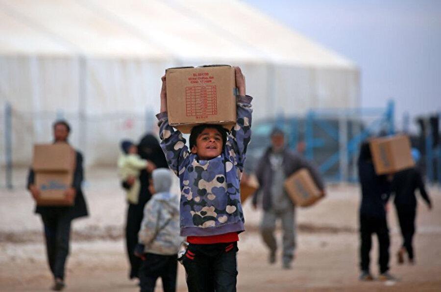 Haseke mülteci kampında yaşayan Suriyeli çocuk, UNICEF tarafından dağıtılan insani yardım paketini ailesine götürüyor.