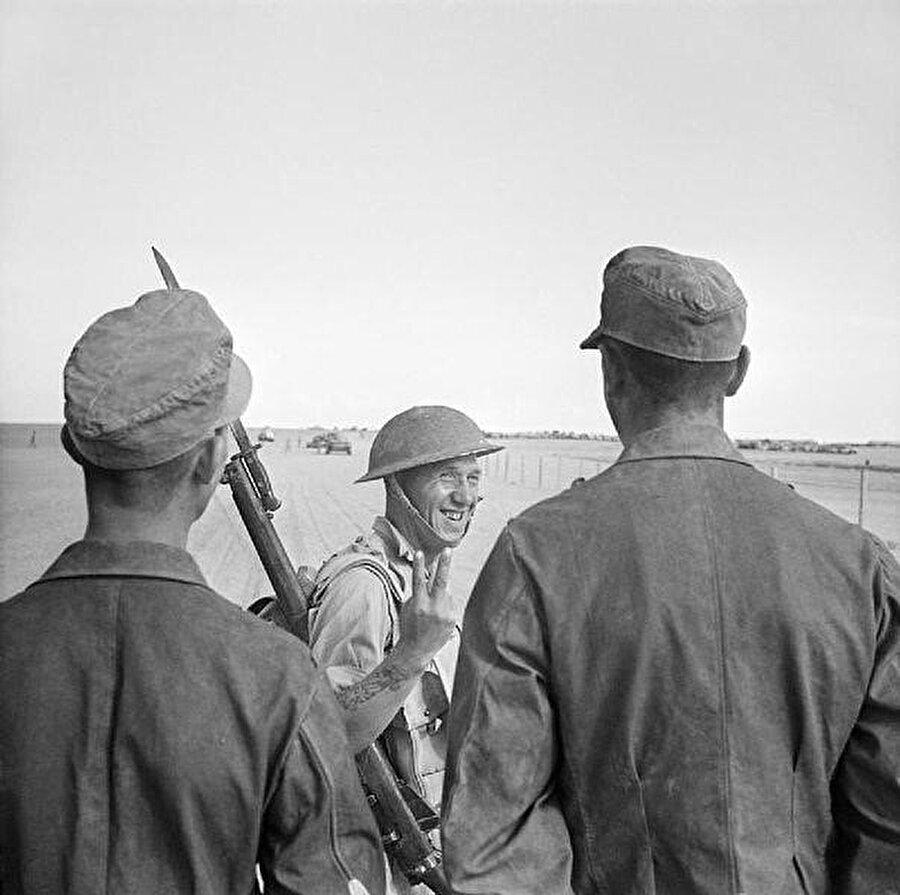 Bir İngiliz askeri el-Alemeyn'de esir alınan Alman tutsaklara zafer işareti yapıyor. (26 Ekim 1942)