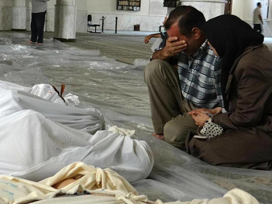2013'te Doğu Guta bölgesine düzenlenen kimyasal saldırıda yakınlarını kaybeden Suriyeli çift ölenlerin başında yas tutuyor.
