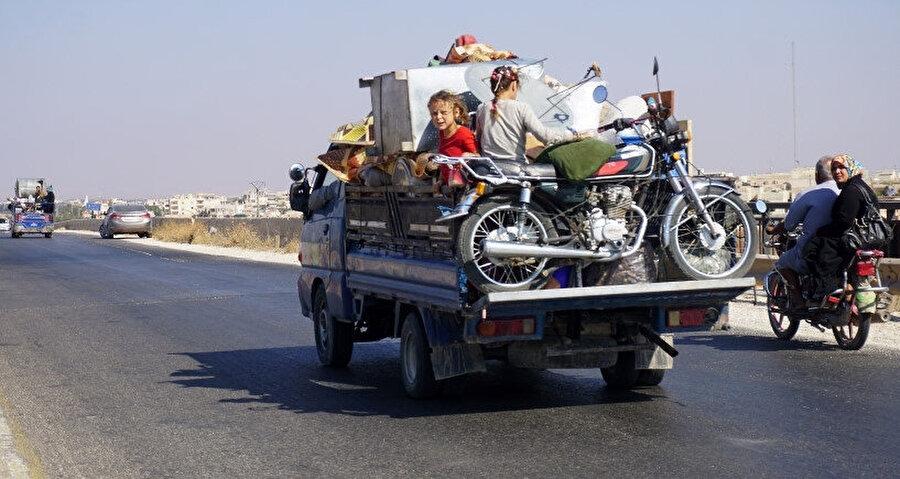 Yanlarına alabildikleri eşyalarla daha güvenli bölgelere göç etmek için yollara düşen Suriyeli bir aile.