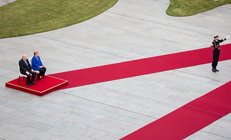 Angela Merkel, daha önce titremesiyle çok konuşulmuştu. Aynı görüntülerle gündeme gelmek istemeyen Merkel, karşılama töreninde yine oturmayı tercih etti. -REUTERS