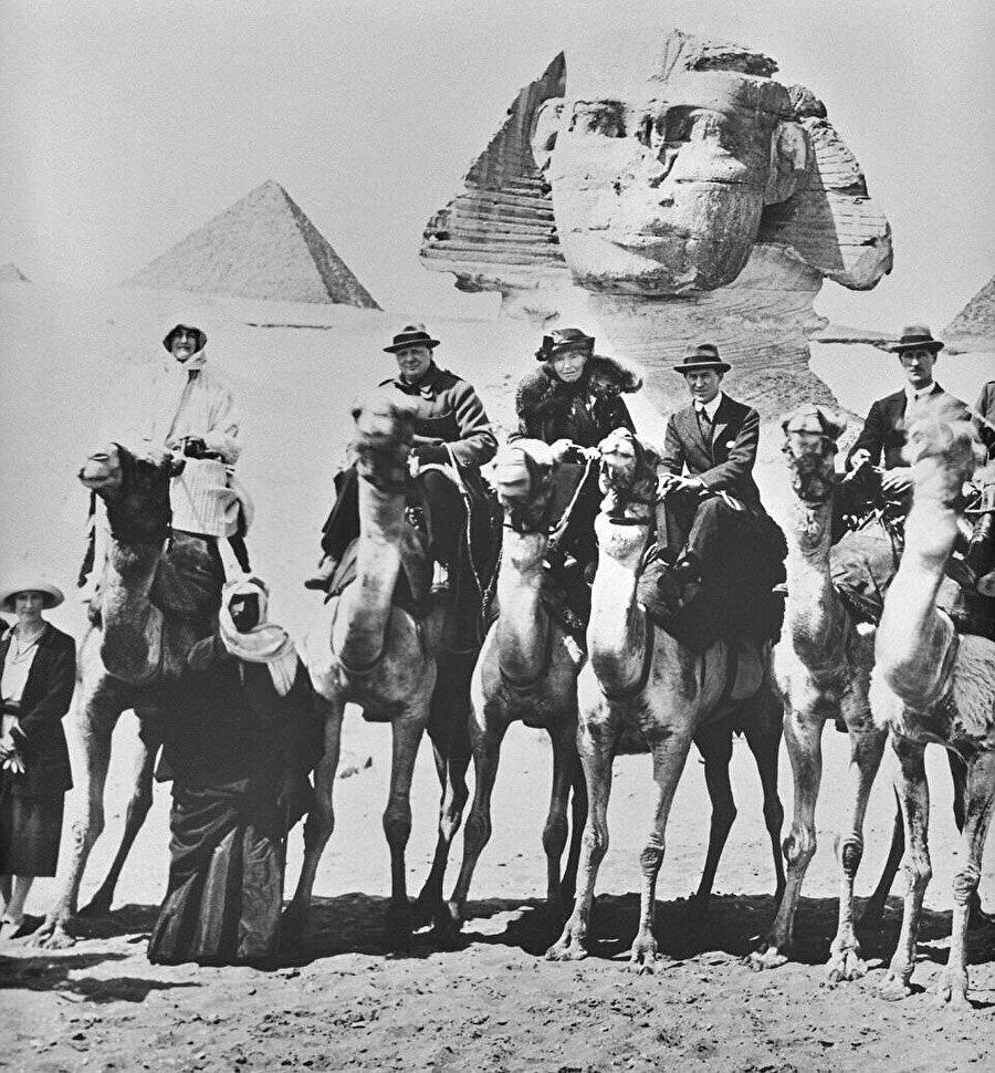 """Ortadaki üçlü soldan sağa, Churchill, """"Arabistanlı Lawrence"""" ve Gertrude Bell Mısır'da sfenksin önünde poz veriyor, 15 Şubat 1921."""