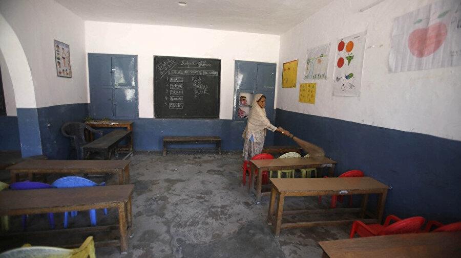 Hindistan kontrolündeki Keşmir'de okul çalışanları terk edilmiş sınıflarda temizlik yapıyor. Hindistan hükumeti zamanla, kesilen telefon hatlarının tamir edildiğini ve güvenlik önlemlerinin hafifletildiğini iddia etse de Keşmir'in büyük bir kısmında kısıtlamalar devam ediyor.