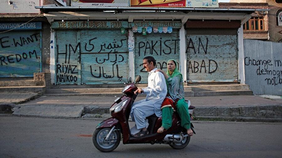 Keşmirli çift, Srinagar'daki kısıtlamalar sırasında üzeri grafitilerle dolan kapalı dükkanların önünden geçiyor.