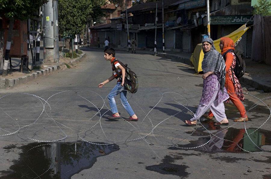 Kısıtlamaların devam ettiği Keşmir'de, Hindistan güçlerinin çektiği bariyerin önünden geçen, annelerinin eşlik ettiği Keşmirli çocuklar.