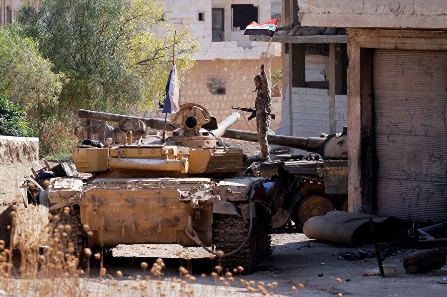Rejim askeri elinde Suriye bayrağıyla görünüyor.