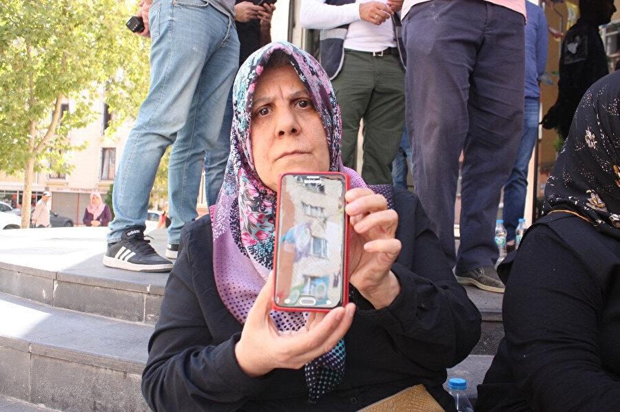 Oturma eylemine katılan annelerden biri oğlunun fotoğrafını gösteriyor.