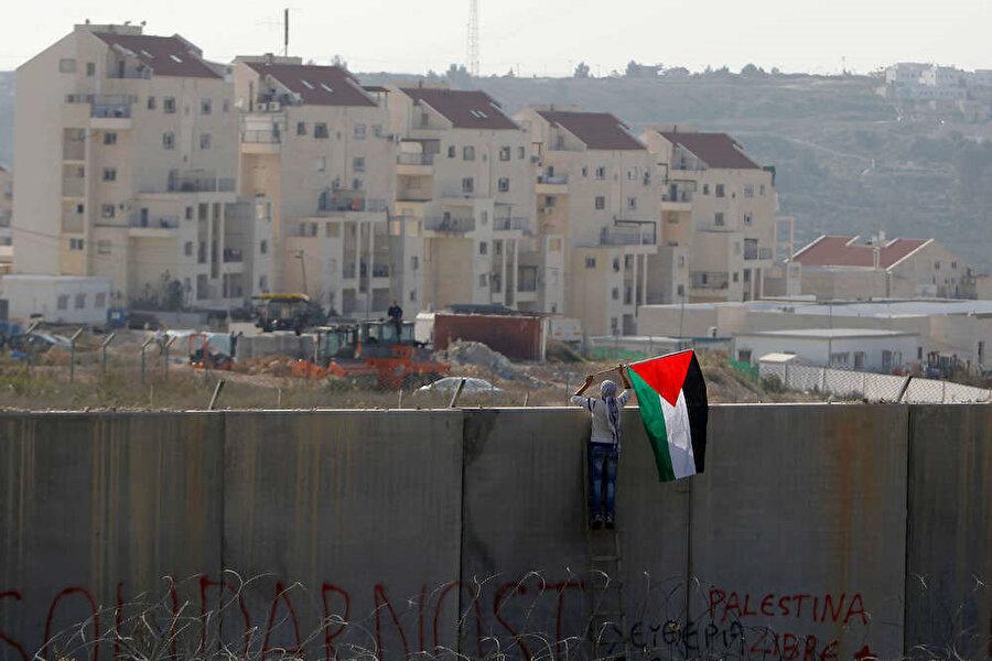 Ayrılık duvarına Filistin bayrağını yerleştiren Filistinli genç, yasa dışı Yahudi yerleşim birimleriyle karşı karşıya.
