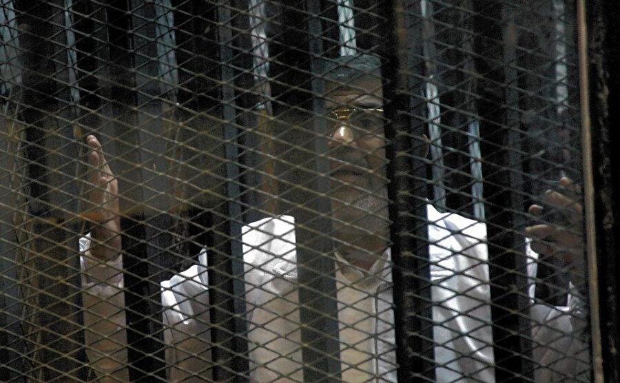 """Muhammed Mursi, 2011'de Hüsnü Mubarek'in devrilmesine yol açan devrimin yarattığı kaosun ortasında """"hapishane baskını"""" organize etmekle suçlandığı davada yargılanırken."""