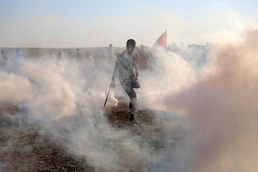 Ampute bir Filistinli Gazze Şerinde düzenlenen protesto sırasında göz yaşartıcı gazdan kaçmaya çalışıyor. Filistin Sağlık Bakanlığı'na göre, 2018 yılında İsrail saldırılarında alt uzuvlarından yaralan binlerce kişi var.