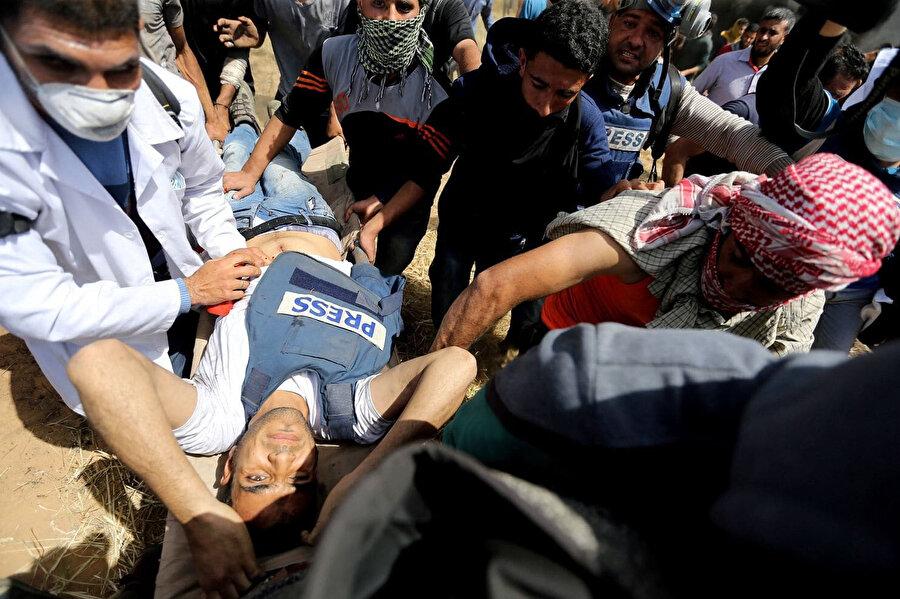 İsrail güçleri tarafından karnından vurulan bir gazeteci.