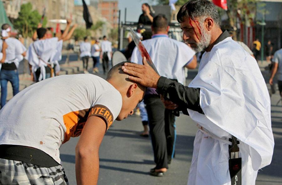 Aşure günü düzenlenen yas merasiminde başlarına kılıç vurduran Iraklı Şiiler.