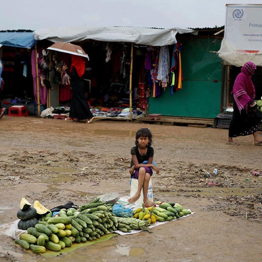 Bangladeş'te buluna kamplarda sebze satmaya çalışan Myanmarlı mülteci çocuk. Kamplarda bulunan çocukların özellikle kızların eğitim hizmetlerinden yararlanma olanakları oldukça kısıtlı.