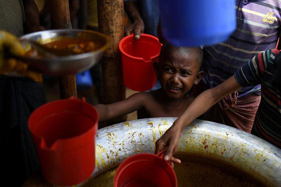 Bangladeş'teki mülteci kampında yemek kazanına uzanan Arakanlı bir mülteci çocuk.