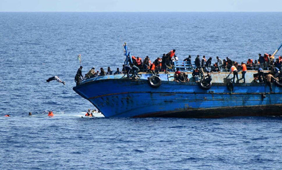 Batmak üzere olan bir tekneden atlayan mülteciler.