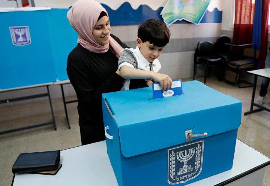 Seçimlerde oğluyla birlikte oy kullanan Arap kökenli bir İsrail vatandaşı.