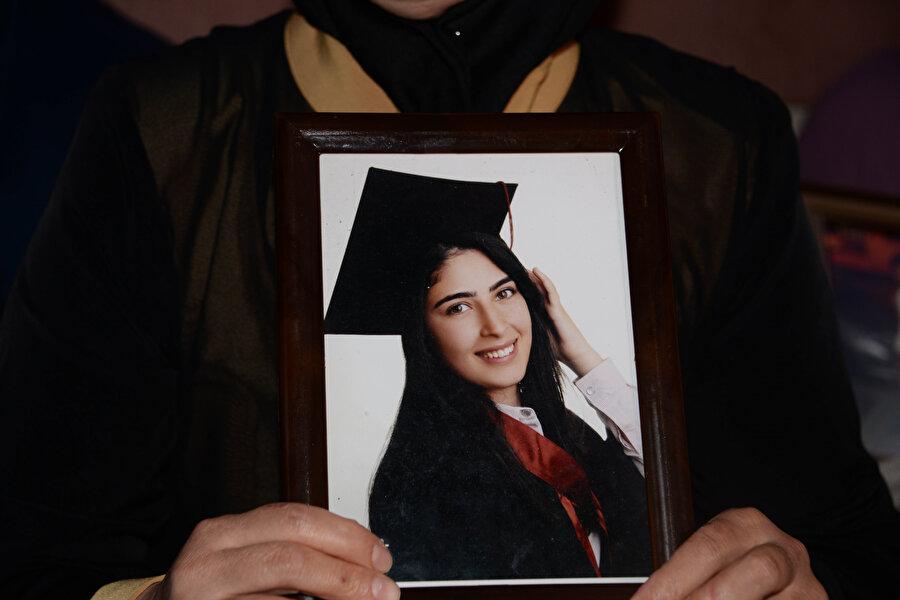 Türkan Mutlu kızı Şeyma'nın fotoğrafını elinde tutarken görünüyor.