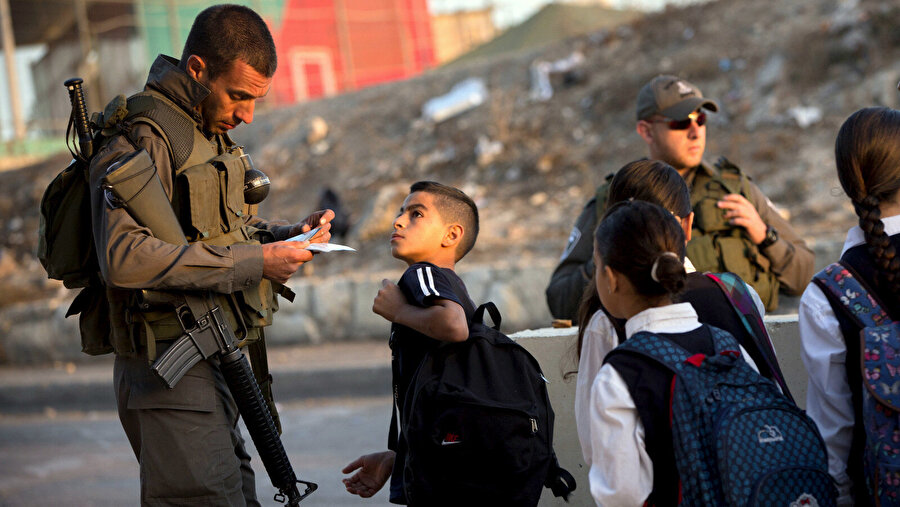 Filistinli çocuklar her sabah İsrail kontrol noktalarında gerekli belgeleri gösterip, çantaları arandıktan sonra okula gidebiliyor.