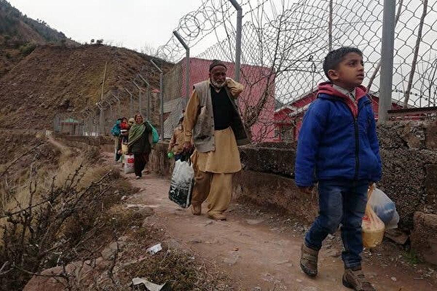 Keşmirli köylüler sınır hattından geçerken endişe duyuyorlar.