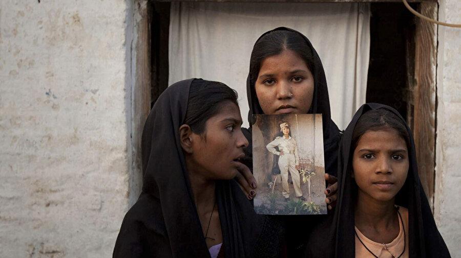 Asya Bibi'nin kızları, evlerinin önünde annelerinin fotoğrafıyla poz veriyor.