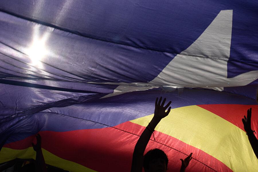 Gösteriler sırasında insanlar bayrağın altında görünüyor.