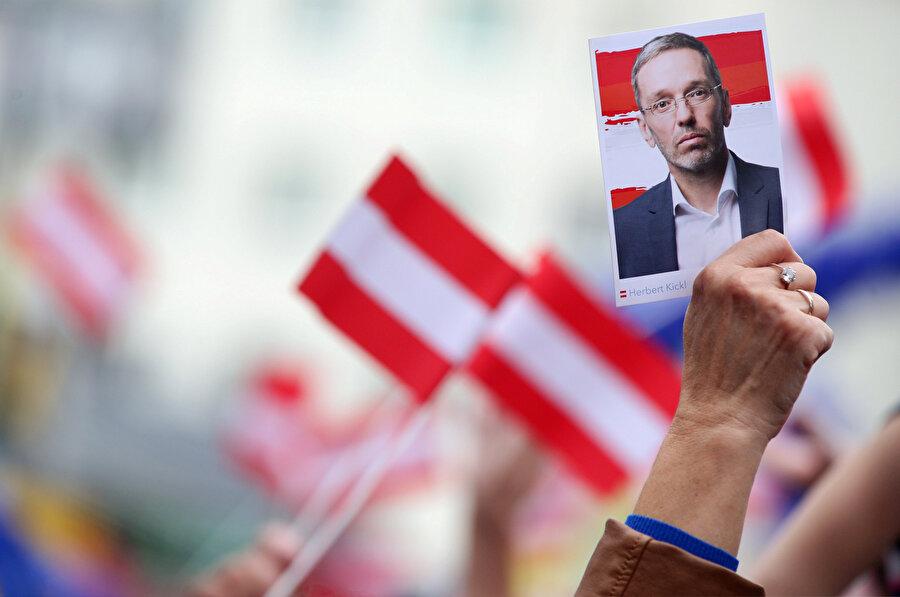 Bir destekçi, eski İçişleri Bakanı Herbert Kickl'in fotoğrafını kaldırırken görünüyor.