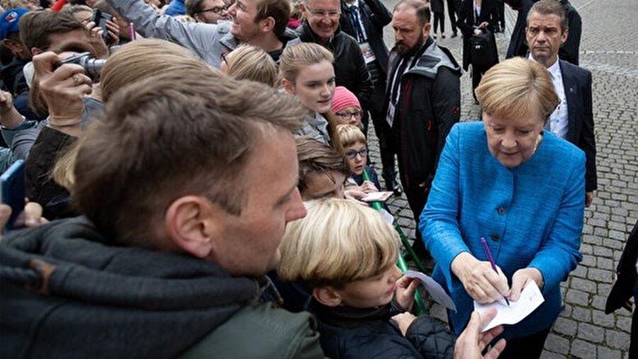 Şansölye Merkel, tören alanındaki bazı sevenlerine imza verdi.