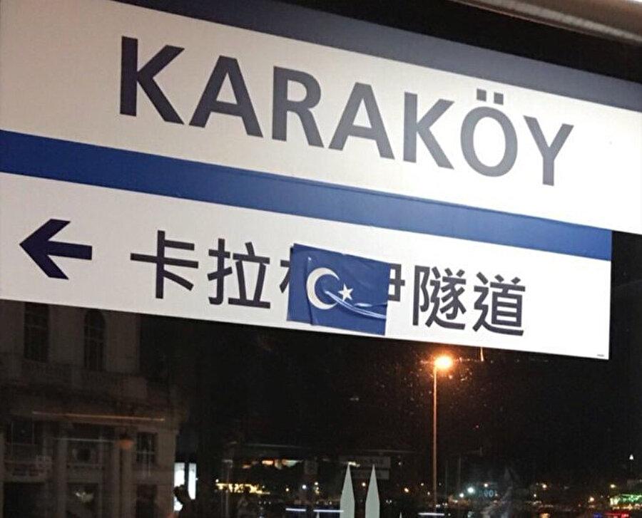 Çince yönlendirme tabelasının üstüne Doğu Türkistan bayrağı yapıştırıldı.