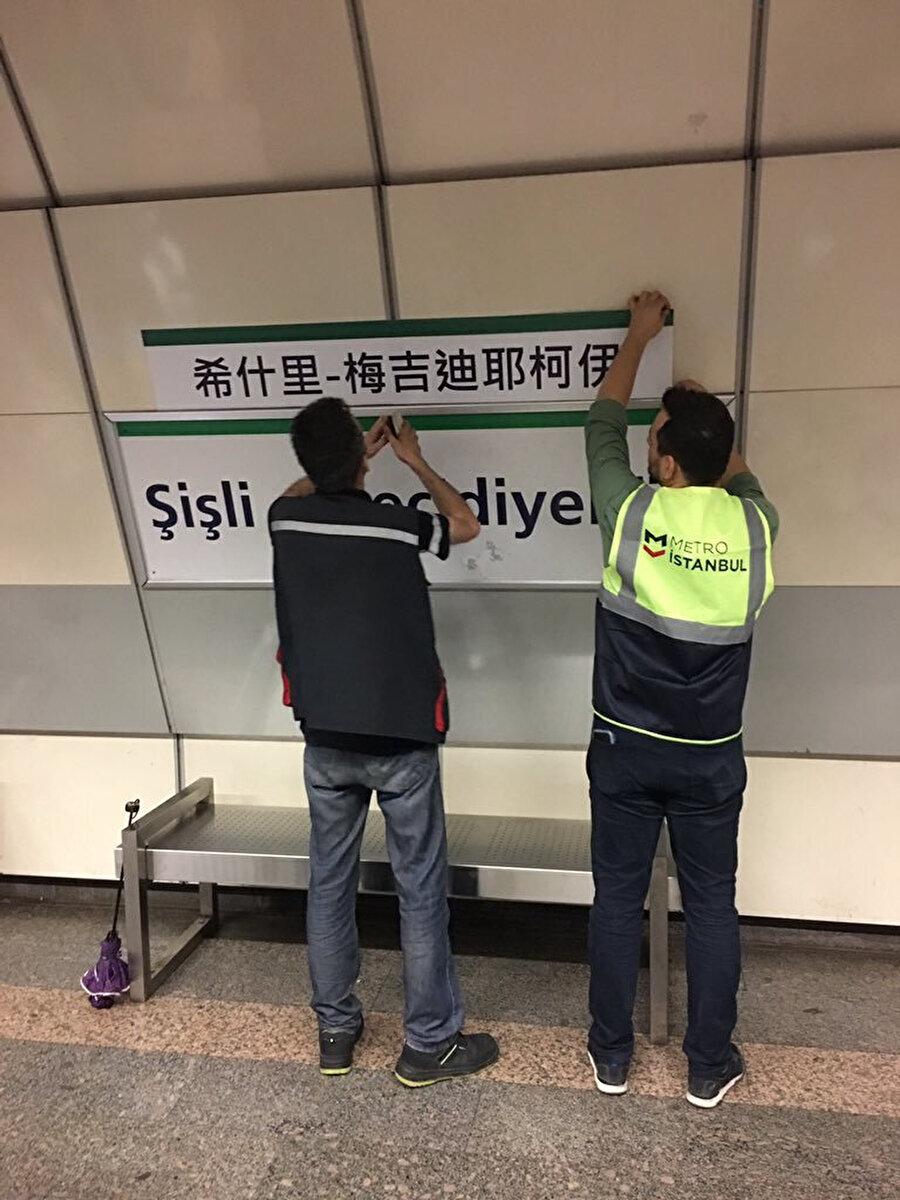 İBB çalışanları Çince tabelayı asarken görünüyor.