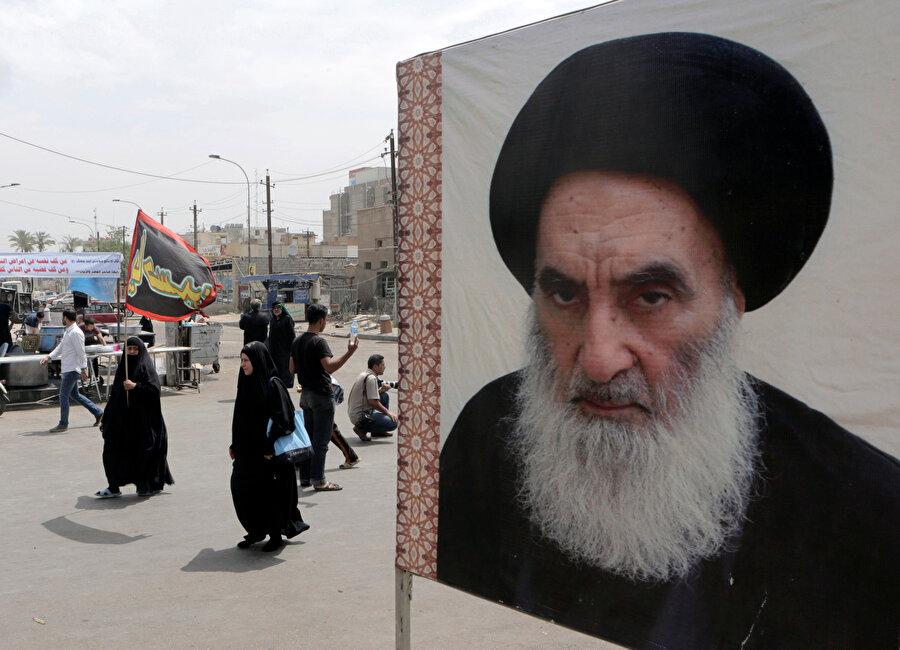 Sağ tarafta Şiilerin en büyük dini lideri Ali es-Sistani'nin posteri görülüyor.