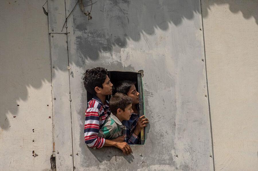 Keşmirli çocuklar, protestocular ve güvenlik güçleri arasındaki çatışmaları izliyor.