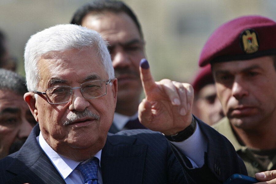 2012'de düzenlenen yerel seçimlerde Mahmut Abbas oy kullandıktan sonra kameralara mürekkebe batırdığı parmağını gösteriyor.