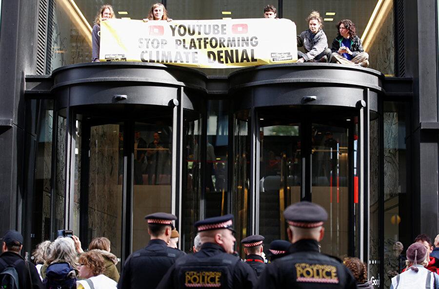 Protestocular, bir iş yerini işgal ettikleri sırada ellerinde bir pankartla görünüyor.