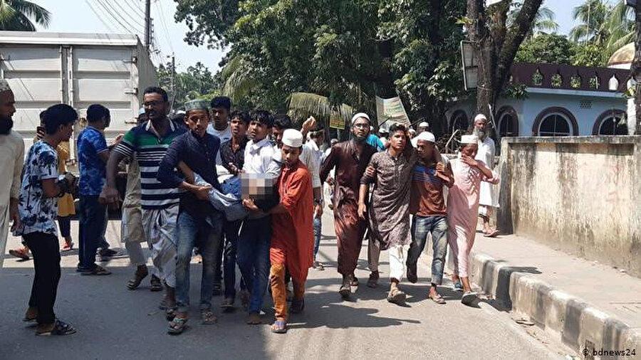 Yaralı arkadaşlarını hastaneye taşıyan göstericiler.