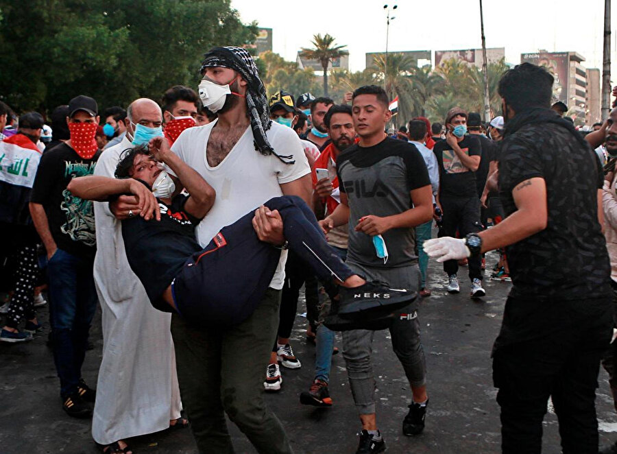 Gösterilerde yaralanan protestocu, arkadaşı tarafından hastaneye taşınıyor.