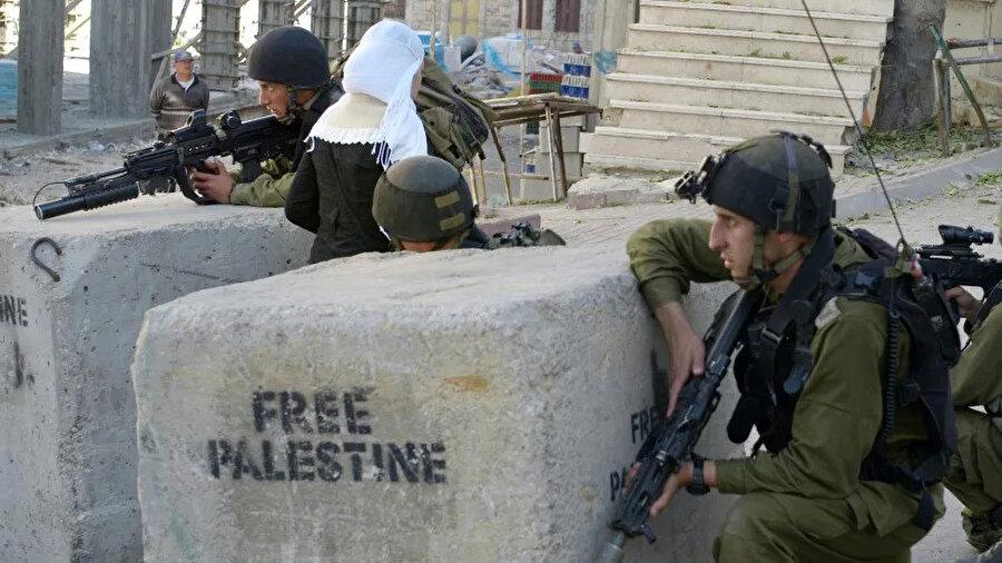 Batı Şeria'daki İsrail askerleri, Özgür Filistin yazan beton blokların arasında.