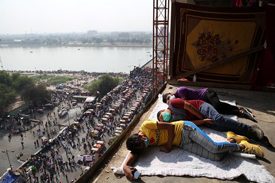 Gece gündüz binada nöbet tutan göstericiler, nöbetleşe uyurken görülüyor.