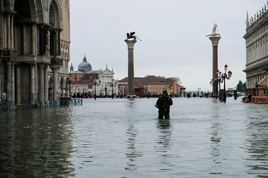 Sular altında kalan San Marco meydanında bir turist etrafı seyrediyor.