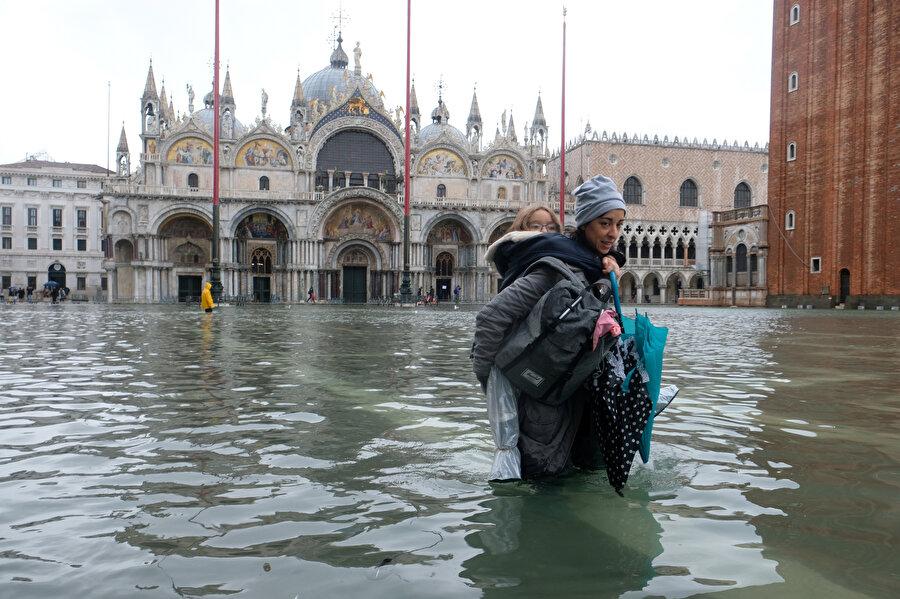 Venedik'te çocuğunu sırtına alıp yürüyen bir kadın