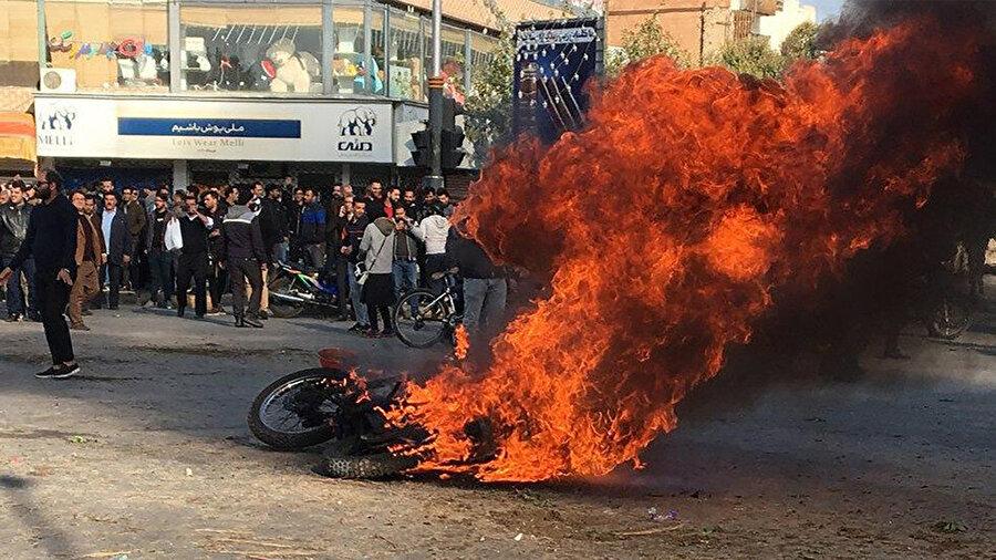 Gösteriler sırasında ateşe verilen bir motosiklet.