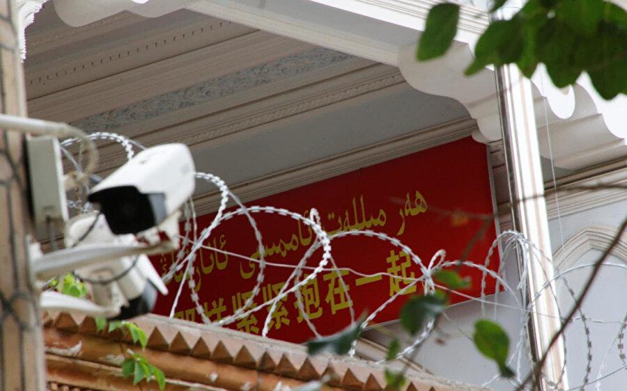 Uygurların yaşadığı bölgede bir caminin duvarına asılan propaganda metni ve güvenlik kamerası.