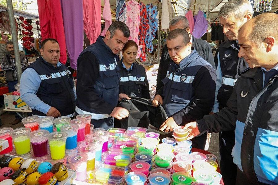 Zabıtalar semt pazarında slime hamurlarını tezgahlardan toplarken