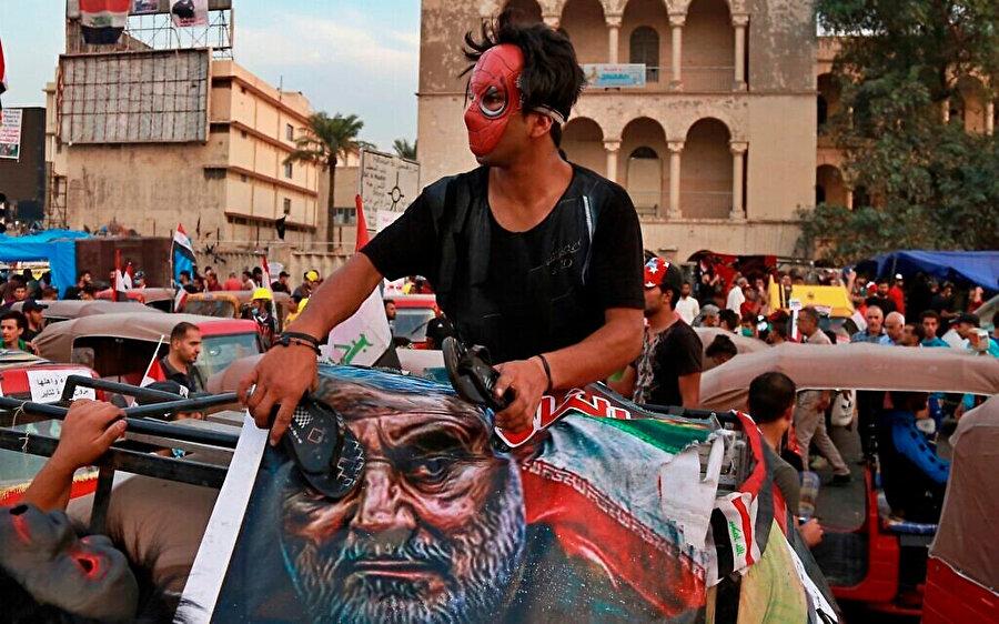 Devrim Muhafızları'na bağlı Kudüs Gücü Komutanı Kasım Süleymani'nin posterine terlikle vuran bir gösterici.