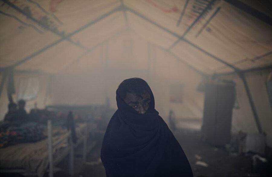 Derme çatma barınaklarda yaşayan mültecilerden biri çadırı ısıtmak için yakılan ateşin dumanıyla dolu odada objektiflere yansıyor.