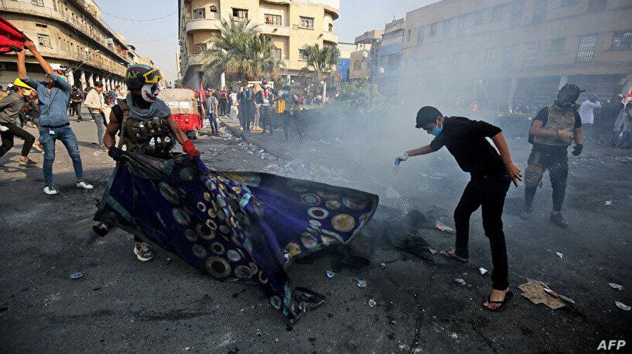 Polisin attığı göz yaşartıcı gazı battaniye ile örtmeye çalışan göstericiler.