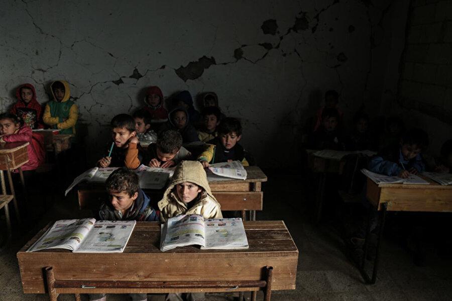 Suriyeli çocuklar, İdlib'de hasarlı Al Kefir okulunda sınıflarında ders görüyor. Suriye rejiminin 2015-2016 yılları arasında gerçekleştirdiği saldırıların yol açtığı yıkıma rağmen 200'den fazla öğrenci okula devam ediyor.