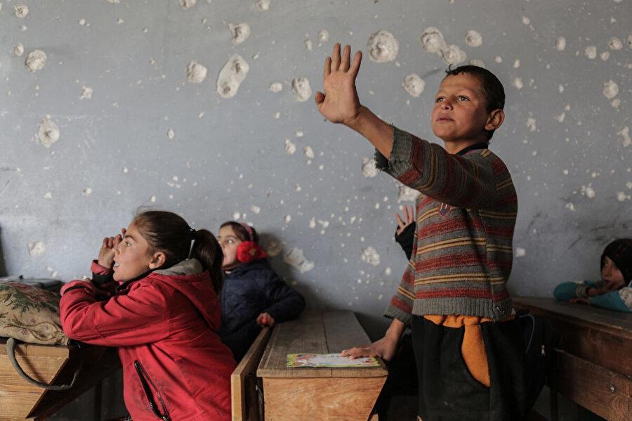 Delik deşik olmuş duvarlara rağmen çocuklar sınıf kurallarını uyarak ders katılıyor ve söz alırken ellerini kaldırıyorlar.