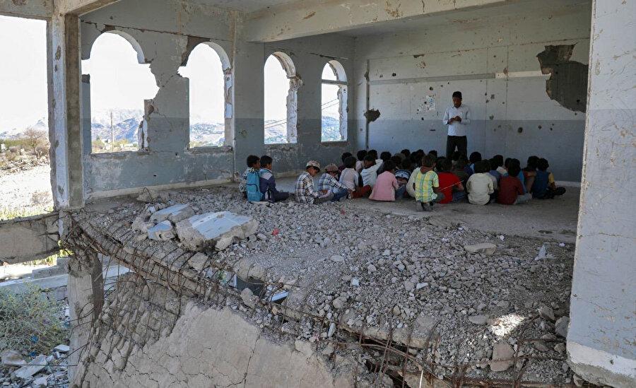 Yemenli çocuklar, yeni akademik yılın ilk gününde, öğretmenlerini, hava saldırılarında ağır hasar gören bir sınıfta dinliyorlar.