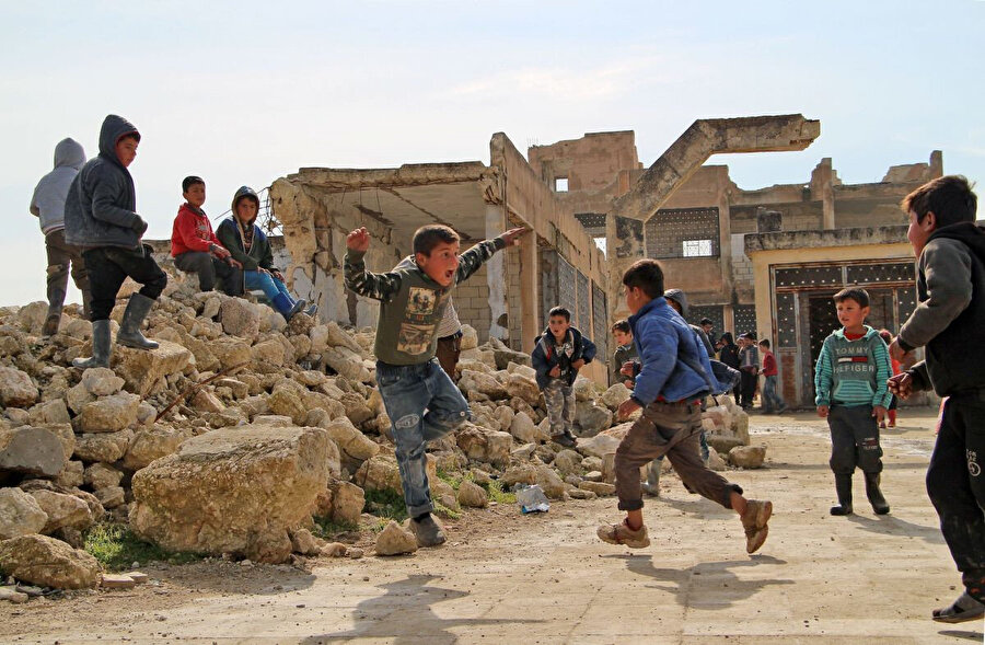 4 Şubat 2019'da çekilen bu fotoğrafta çocuklar, Suriye'nin İdlib kentine bağlı Kufayr köyünde, çatışmalara sırasında kısmen tahrip olmuş bir okulun bahçesinde oynuyorlar.