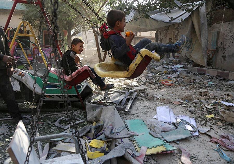 Şam'a bağlı Doğu Guta'da saldırılarda zarar gören okullarının bahçesindeki oyun parkında sallanan Suriyeli çocuklar.